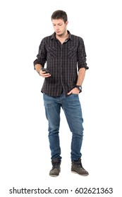 Cool relaxed young casual man typing message on mobile phone.  Full body length portrait over white studio background.
