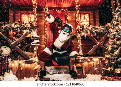 Cool rocker in Santa Claus costume and luminous glasses plays the guitar near a festively decorated house.