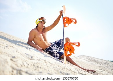 Cool sand-boarder having a rest before his next extreme downhill