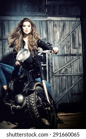 Cool sensual biker girl in black leather jacket and blue jeans sitting on old fashioned motorcycle in garage interior on grey wooden wall background, vertical picture