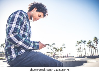 Cool skateboarder outdoors - Afroamerican guy listening music on his smartphone