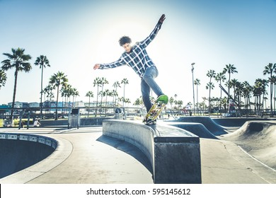 Cool skateboarder outdoors - Afroamerican guy jumping with his skate and performing a trick