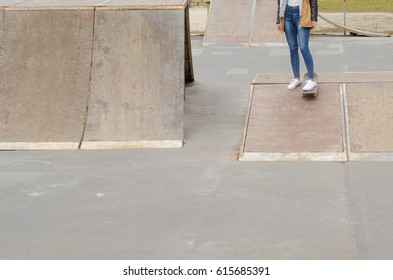 Cool skater girl riding a long board at the city