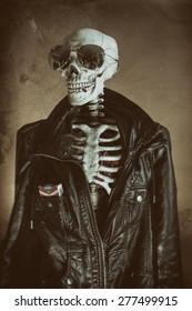 Cool Skeleton Vintage. A cool skeleton wearing a leather jacket and sunglasses, with cigarettes in his pocket and a smoke in his mouth. His heart visible in his ribcage. Edited in vintage film style.