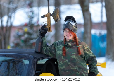 Cool smiling girl with paintball marker posing near car