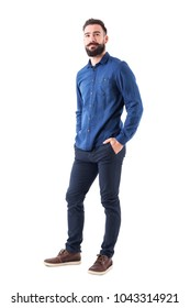 Cool smiling guy, with hands in pockets looking up wearing blue denim shirt and pants. Full body isolated on white background.