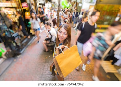 Cool style young asia woman enjoy shopping at street outdoor market in Daytime. She smile and Hand holding shopping bag with blur bokeh asia fashion market background
