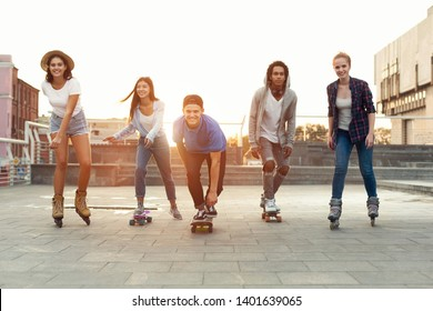 Cool teen friends. Happy teenagers having fun, riding on skateboards and rollers on summer evening