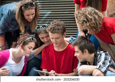 Cool teenagers reading on a tablet computer