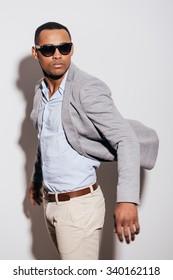 Cool and trendy. Confident young African man in sunglasses wearing jacket and looking over shoulder while standing against white background