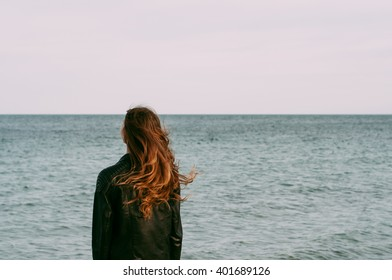 cool trendy stylish lonely girl looking at the calm sea on the sunset with wind in her hair back view