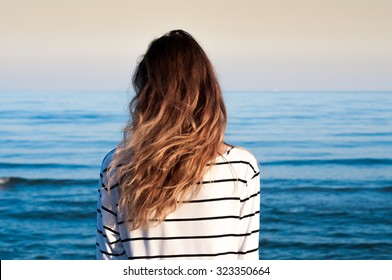 cool trendy stylish sexy blonde lonely girl looking at the calm sea on the sunset with wind in her hair and  seagulls on background