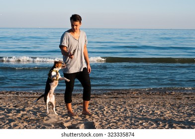 cool trendy stylish sexy handsome happy hipster guy having fun playing with his beagle puppy dog on the beach sea background