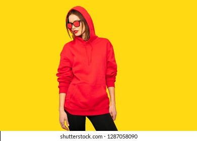 cool and tuff hipster girl with sunglasses posing in red hoodie on yellow background