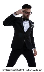 cool unshaved guy in tuxedo looking down and pointing fingers to head standing and posing isolated on white background