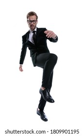 cool unshaved man in black suit holding knee up, marching and frowning, posing isolated on white background, full body