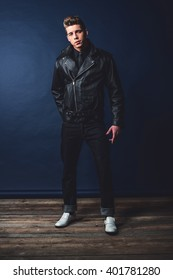 Cool vintage rock and roll 1950s fashion man wearing black leather jacket and jeans.