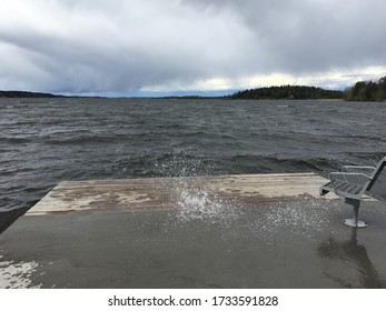 Cool water splash on a stormy day. Gray clouds and the wind is blowing hard. A bridge next to water, and the water splashes up high. Sandviksbadet, Stockholm, Sweden, Europe. Forest in background.