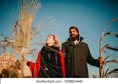 Cool and weird young couple posing outdoors while holding palm tree branches.