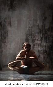 cool yoga man posing on dirty grunge background