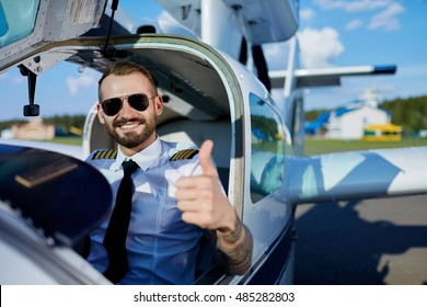 Cool young adult pilot showing thumb up with a toothy smile