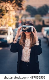 cool young beautiful girl testing virtual reality 3D video glasses VR headset dressed in a office outfit impressed by augmented reality on the street with beautiful autumn sun light colors