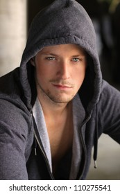 Cool young dude in grey hooded jacket with sexy smirk on his face
