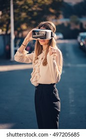 Cool young girl adjusting her virtual reality headset VR glasses on the street and she is feeling curious in augmented reality with beautiful autumn morning sunrise light with hand raised