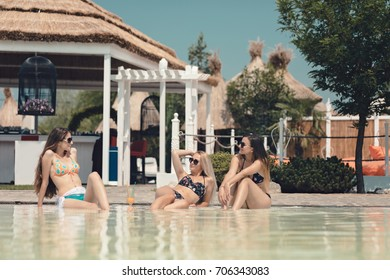 Cool young girls best friends on amazing holiday share drinks and cocktails near pool wearing sunglasses having fun and feeling happy in summer outfit on the island resort. Beach bar on background