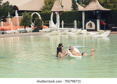 Cool young girls enjoy the beautiful summer pool and the excellent sun while tanning on the floating sunbed.Dream the perfect holiday in amazing seaside resort sunbathing and being happy in the nature