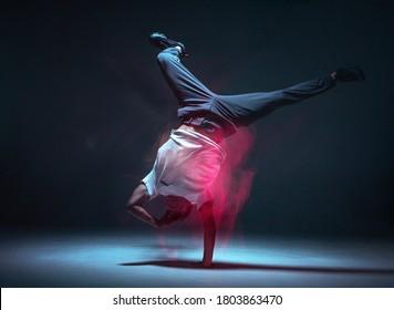 Cool young guy breakdancer dancing hip-hop in neon light. Dance school poster. Long exposure shot