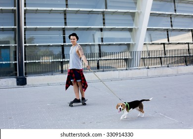 cool young and handsome caucasian brunette hipster skater guy wearing a hat posing smiling and having fun outside while skating with his skateboard summer day in the city with beagle puppy dog
