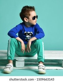 Cool young kid boy in blue aviator sunglasses, blue shirt with raccoon print, green sweatpants and white sneakers sitting on white wooden pallet on a playground looking aside
