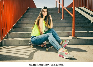 Cool young long haired girl sitting on skateboard near the urban stairs. Active lifestyle funky in summer. Trendy sport teen.