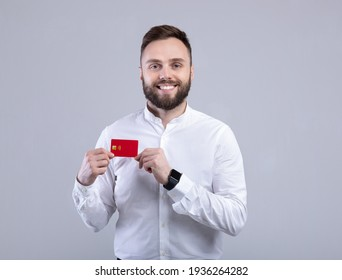Cool young man in office wear holding credit card and smiling at camera on blue studio background