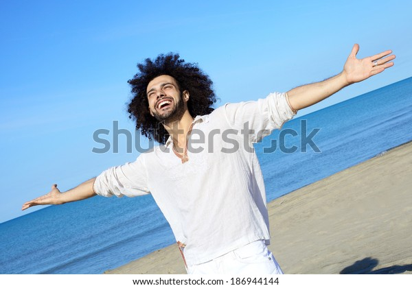 Cool young man with open arms having fun on beautiful beach