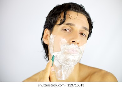 Cool young man shaving with blade