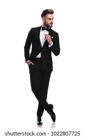 cool young man in tuxedo is thinking and looks to side with one hand in pocket on white background