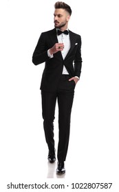 cool young man in tuxedo wearing ring is walking and looks to side , isolated on white background
