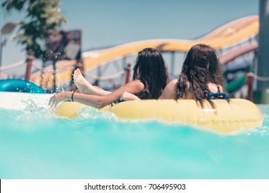 Cool young people having fun on the water slide with friends and familiy in the aqua fun park glides are happy and water splashes are all over. Blue sky background looks amazing sunlight