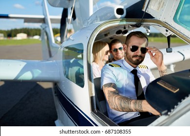Cool young pilot and happy couple sitting in cabin of private air plane to fly on a vacation in summer
