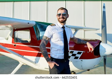 Cool young pilot in sunglasses posing at private motor airplane on runway near hangar.