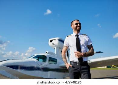 Cool young pilot in sunglasses with tattoos on his hands posing at private air plane on runway. Good summer weather, handsome male model