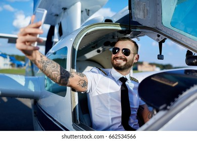 Cool young pilot take a selfi with his smart phone sitting in air craft cabin. Handsome man with tattoos