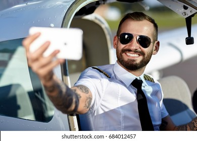 Cool young pilot take a selfie with his smart phone sitting in air craft cabin. Handsome man with tattoos
