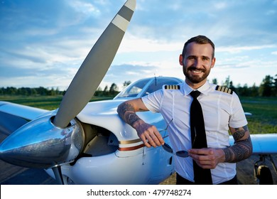 Cool young pilot with tattoos posing at small private motor airplane standing on runway at bright sunset. Blue sky, bright sun