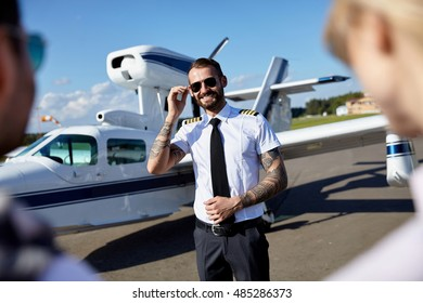 Cool young pilot with tattoos in uniform welcomes tourists couple to fly on private motor air plane. Summer traveling is fun