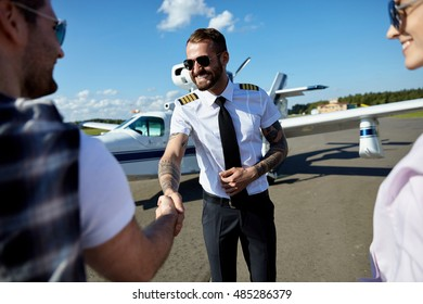 Cool young pilot in uniform welcomes tourists couple to fly on private motor air plane. Summer traveling is fun