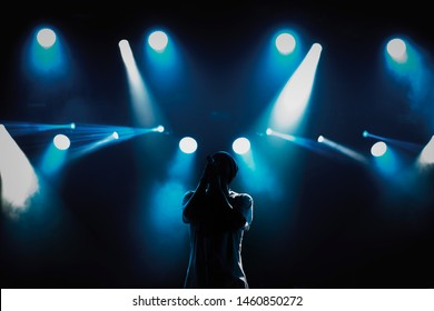 Cool young rap singer with microphone on bright backlit stage in bright blue lights.Hip hop star performing solo set on scene in music hall.Popular rapper sings a song on rock festival in nightclub