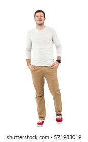 Cool young stylish man laughing with hands in pockets looking at camera. Full body length portrait isolated over white studio background.